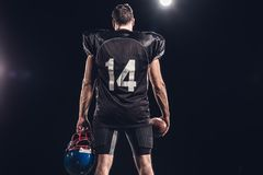 rear view of american football player with ball and helmet under spotlight