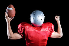 Rear view of American football player cheering while holding ball Royalty Free Stock Photos