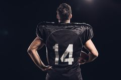 rear view of american football player with helmet in hand