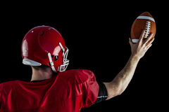 Rear view of american football player holding up football Stock Image