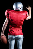 Rear view of American football player pointing while holding ball Stock Photo