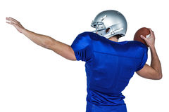 Rear view of American football player throwing ball Royalty Free Stock Photos