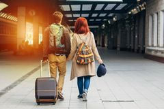 Rear view of amorous hipster couple walking down station and chatting outdoors. Holyday concept. Rear view of amorous hipster couple walking down station and Stock Photo
