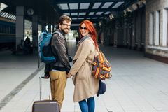 Rear view of amorous hipster couple walking down station and chatting outdoors. Holyday concept. Rear view of amorous hipster couple walking down station and Stock Photos