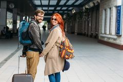Rear view of amorous hipster couple walking down station and chatting outdoors. Holyday concept. Rear view of amorous hipster couple walking down station and Stock Images