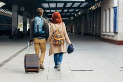 Rear view of amorous hipster couple walking down station and chatting outdoors. Holyday concept. Rear view of amorous hipster couple walking down station and Royalty Free Stock Image