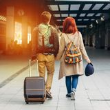 Square photo.Rear view of amorous hipster couple walking down station and chatting outdoors. Holyday concept. Rear view of amorous hipster couple walking down royalty free stock photography