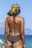 Rear View of Arab Woman at the Beach. Rear view of a young woman wearing swimsuit and silk scarf , standing at the beach and looking out at blue sea Stock Images