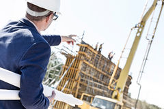 Rear view of architect holding blueprints while pointing at construction site Stock Photo
