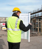 Rear view of architect looking down at plans. Architect or engineer at work on a building site. Checking plans against the construction work. Back to camera Royalty Free Stock Images