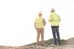Rear view of architects standing at construction site against clear sky Royalty Free Stock Photo