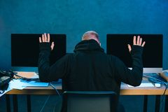 rear view of arrested hacker with raised hands in front royalty free stock photography