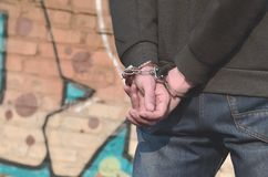 Rear view of the arrested and handcuffed offender against the gr. Affiti background. The concept of preventing property damage, vandalism and combating stock photography