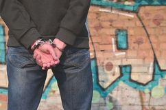 Rear view of the arrested and handcuffed offender against the gr. Affiti background. The concept of preventing property damage, vandalism and combating royalty free stock photo