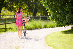 Rear View As Woman Pushes Bike Along Lane Royalty Free Stock Image