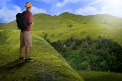 Rear view of asian backpacker standing on the hill peak Stock Image