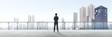 Rear view of asian business woman standing on modern terrace and looking at view royalty free stock images
