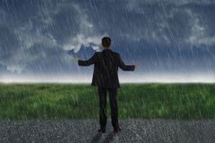 Rear view of asian businessman standing on the rain. With dark sky background royalty free stock photography