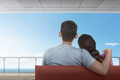 Rear view of asian couple sitting on couch and enjoying ocean vi. Ew from balcony stock images