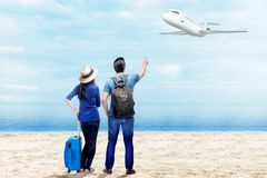 Rear view of asian couple with suitcase bag and backpack standing on the beach royalty free stock image