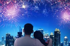 Rear view of asian couple watch the fireworks. On the city royalty free stock images
