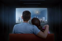 Rear view of asian couple watching celebration on tv. At dark room stock image