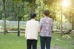 Rear view Asian elderly women walking in garden park Stock Photos