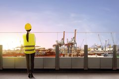 Rear view of asian female worker with safety vest and hard hat standing on office terrace and looking at dock. With sunset view background royalty free stock image