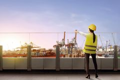 Rear view of asian female worker with safety vest and hard hat standing on office terrace pointing and looking at dock. With sunset view background royalty free stock photos
