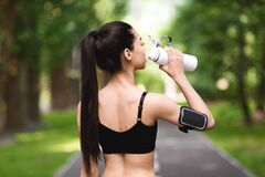 Rear view of asian fitness woman drinking water after jogging in park