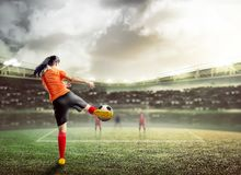 Rear view of asian football player woman in orange jersey kicking the ball royalty free stock photos