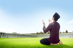 Rear view of asian man sitting in praying position on grass raise the hands and gazing the sky. On the outside the mosque royalty free stock photos