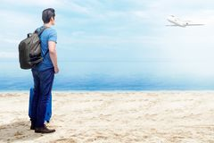 Rear view of asian man with suitcase bag and backpack standing on the beach royalty free stock photos