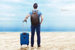 Rear view of asian man with suitcase bag and backpack standing on the beach royalty free stock photography