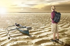 Rear view of asian traveler looking at drying water on the lake stock images