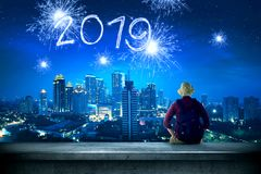 Rear view of asian traveler man sitting on the rooftop looking at 2019 from sparkling fireworks on the city at night stock photo