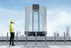 Rear view of asian worker man in safety vest, gloves, yellow helmet and protective mask standing on modern terrace and looking at. Skyscrapers with blue sky royalty free stock photo