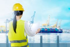 Rear view of asian worker woman with yellow hard hat looking at paperwork on the office. With industrial harbor and blue sky background royalty free stock photo