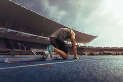 Sprinter resting his feet on a starting block on running track. Rear view of an athlete on his mark ready to sprint on running track. Runner using a starting Royalty Free Stock Photo