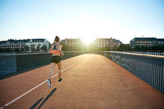Rear view of athlete jogging toward bright sun Stock Photography