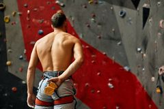 Back side of athlete man standing next to wall, ready for rock climbing. stock image