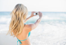 Rear view of attractive blonde in bikini taking a self picture Stock Photo