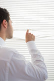 Rear view of attractive businessman spying through roller blind Stock Photos