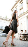 Businesswoman legs walking to meeting. Rear view of an attractive elegant businesswoman walking to a business meeting in a luxury coffee shop terrace Royalty Free Stock Image