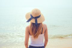 Rear view of an attractive women looking at clear water sea in day . stock photos
