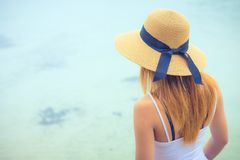 Rear view of an attractive women looking at clear water sea in day . royalty free stock photos