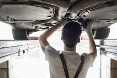 Rear view of automobile mechanic examining car in workshop Stock Photos