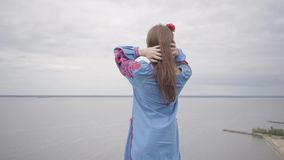 Rear view at carefree caucasian woman wearing long summer fashion dress standing on the field on the background of a. Rear view at awe caucasian woman wearing stock footage