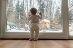 Rear view of baby girl standing in front of dirty window Royalty Free Stock Images