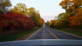 Rear view from back of car driving rural countryside road during autumn day. Car point of view POV behind vehicle country street